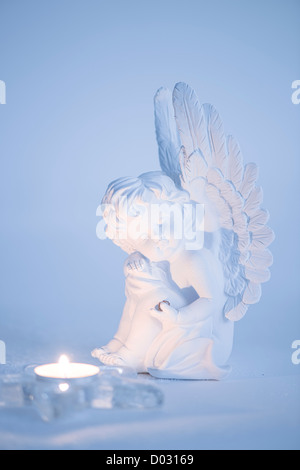 Angel praying and sitting on snow. Hope. Copy space. - Stock Photo
