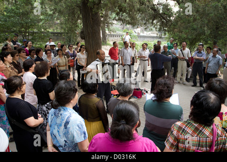A group of residents of Beijing, China, gathering to listen to an accordion player and sing traditional songs in - Stock Photo