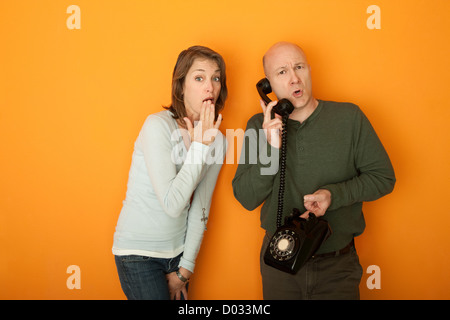 Shocked Caucasian woman with hand on mouth listening to a telephone conversation - Stock Photo
