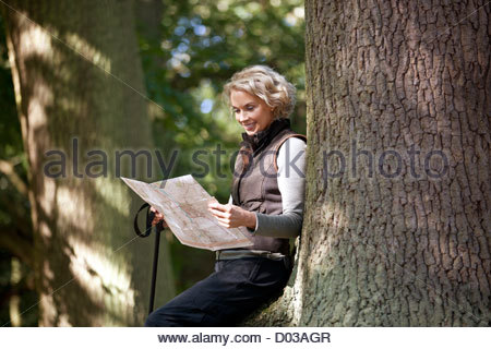 A mature woman resting on a tree, looking at a map, close up - Stock Photo