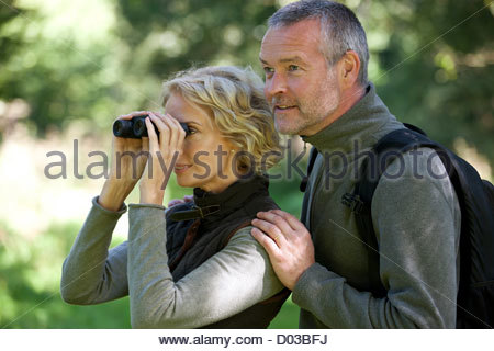 A mature couple outdoors, woman looking through a pair of binoculars - Stock Photo