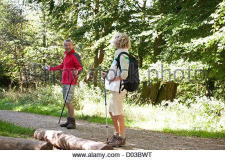 A mature couple walking along a country path, navigating with a smartphone - Stock Photo
