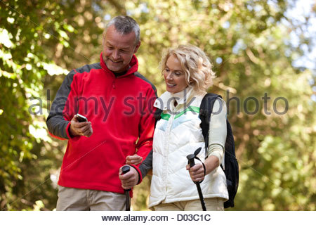 A mature couple walking in the countryside, looking at a smartphone - Stock Photo