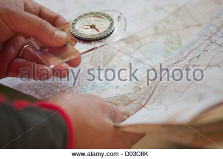 A man holding a map and compass, close up - Stock Photo