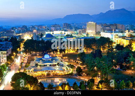 Dusk view of Tirana, the capital of Albania. In the foreground is Rinia Park. - Stock Photo