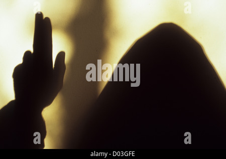 Shadow of hooded monk or priest holding his hand and fingers in benediction before bright window light - Stock Photo
