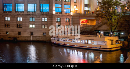 Night photograph of the Chicago River and the Wendella boat dock taken from the lower level Michigan avenue bridge. - Stock Photo