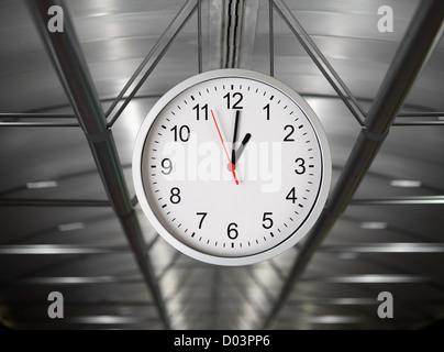 Classical simple clock hanging in industrial interior - Stock Photo