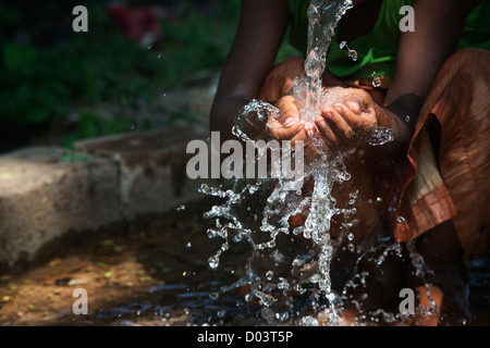 Water from a hand pump in a rural indian village pouring into an Indian girls hands. Andhra Pradesh, India. - Stock Photo