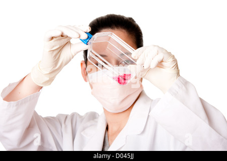 Female scientist researcher looking at red tissue cell culture medium in flask wearing gloves and mouth cap, isolated. - Stock Photo