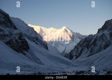 sun on mountains of the snow covered Kang La pass in the Inner Dolpo region of western Nepal - Stock Photo
