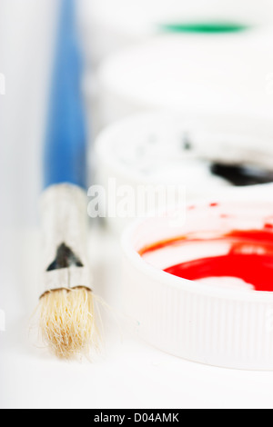 Macro view of brush and covers of gouache paint cans - Stock Photo