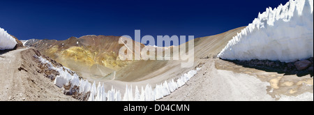 Mountain road cuts through a glacier in the Andes - Stock Photo
