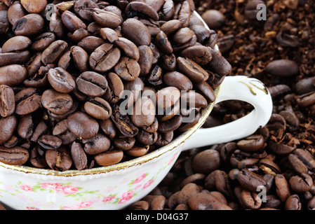 Cup filled with coffee beans over a background of whole and freshly ground coffee beans - Stock Photo