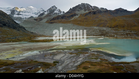 flat glacier lake before entering the reservoir Lac de Moiry in the high mountains of Switzerland - Stock Photo