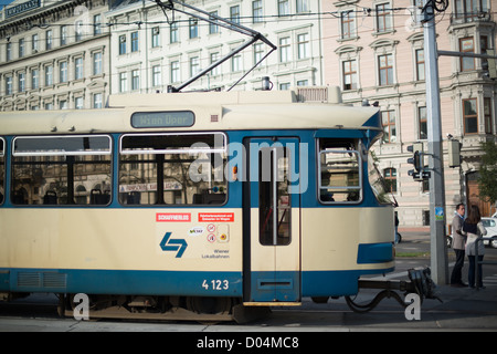 An old blue tram is driving through the town heading to the Vienna Opera on October 5, 2012 in Vienna, Austria. - Stock Photo