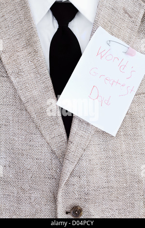 Man's suit jacket, tie and shirt with World's Greatest Dad note pinned over his heart. - Stock Photo