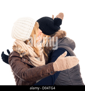 Two young happy friends in winter clothes greeting and hugging, isolated on white background. - Stock Photo