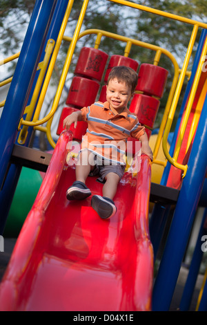 A 2 year old boy plays cheerfully on a red slide in an outdoor playground - Stock Photo