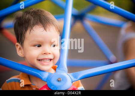 A cheerful 2 year old boy plays on blue monkey bars in outdoor playground - Stock Photo