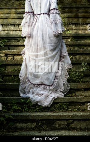 a woman in a wedding dress is walking up old stone stairs - Stock Photo