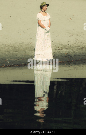 a woman in a floral dress and with a sun hat is standing at a lake - Stock Photo