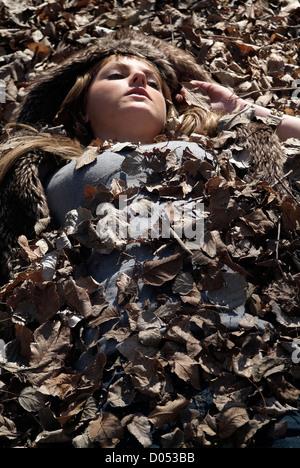 Woman buried in oak leafs - Stock Photo