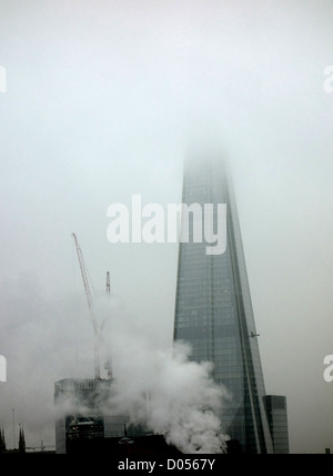 Top of The Shard shrouded in low cloud or fog, London - Stock Photo