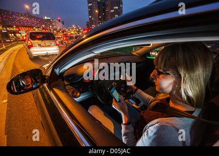 Woman is driving a car. Using a mobile phone. Not allowed while driving a car. - Stock Photo