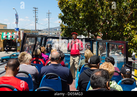 San Francisco - open top hop-on hop-off city tour bus. Guide using microphone. - Stock Photo