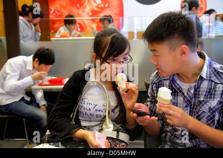 Shanghai China Huangpu District Xizang Road People's Square Raffles City shopping Asian teen boy girl ice cream - Stock Photo