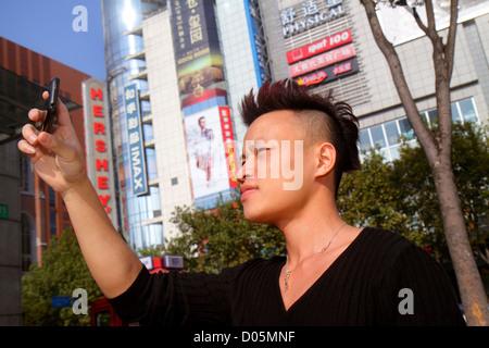 Shanghai China Huangpu District Xizang Road People's Square Raffles City Asian man smartphone camera taking picture - Stock Photo