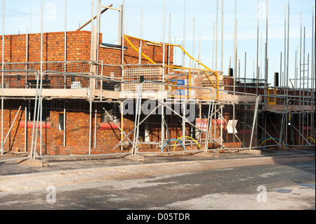 Building site for a new housing estate, UK. Scaffolding around a new house build. - Stock Photo