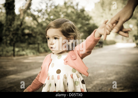 Toddler girl holding on to mother's hand - Stock Photo