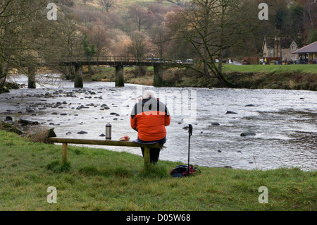 Man sitting on bench, eating picnic by scenic River Wharfe & countryside cafe (Cavendish Pavilion) - Bolton Abbey - Stock Photo