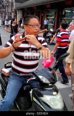 Shanghai China Huangpu District Yuyuan Garden Fuyou Road shopping market marketplace Asian man flute playing electric - Stock Photo