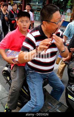 Shanghai China Huangpu District Yuyuan Garden Fuyou Road shopping market marketplace Asian man father flute playing - Stock Photo