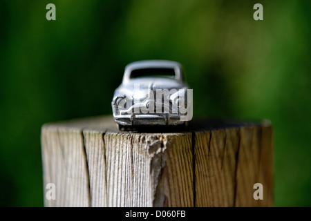 Toy Car. on a wooden garden post - Simca 9 Aronde 1951 24U MECCANO - Stripped of it's paintwork. Background blurred. - Stock Photo