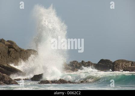 Wave crashing on to rocks, Porthchapel beach, Cornwall, England, UK - Stock Photo