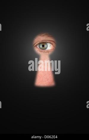 Creepy man peeking through a keyhole with focus on his eyeball. - Stock Photo