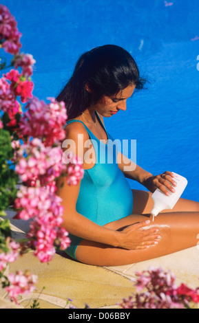 Pregnant woman creaming her legs at swimming pool side - Stock Photo