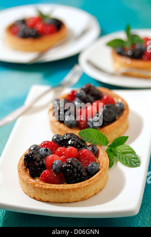 Wild berries tartlets. Recipe available. - Stock Photo