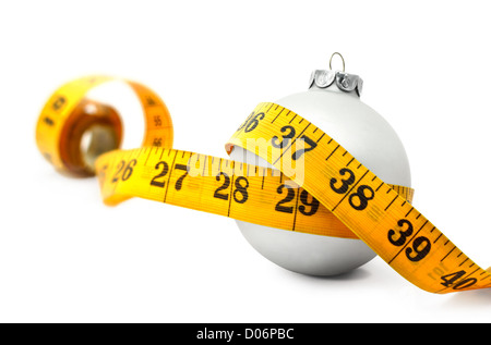 Tape measure around a bauble concept symbolizing Christmas weight gain from eating too much food. - Stock Photo