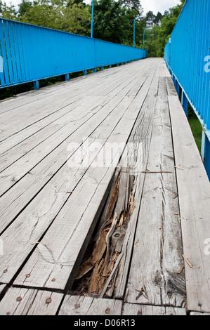chuckhole in old wood bridge of large planks - Stock Photo