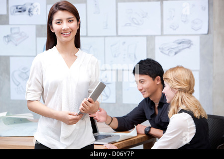 Designer holding digital tablet with his team in background - Stock Photo
