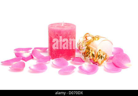 Pink candle with rose leaves and box of chocolate for Valentine's day over white background - Stock Photo