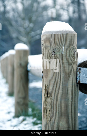 Wooden fence posts in snow. - Stock Photo