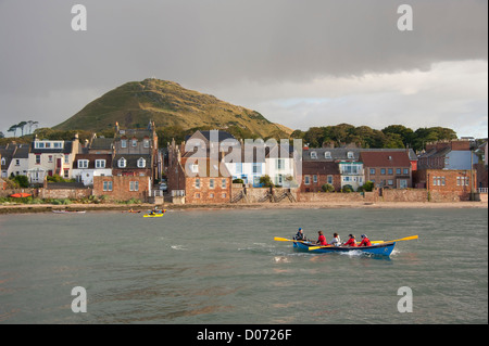 A rowing skiff at North Berwick, with the North Berwick Law (ancient volcano) in the background. East Lothian, Scotland. - Stock Photo