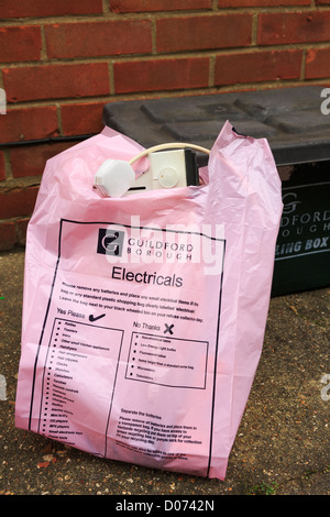 Guildford Borough Council pink plastic recycling bag for household electricals outside a house in Surrey, England, - Stock Photo