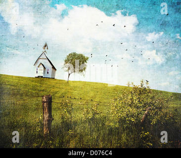 Old country school house  on a hill against a blue sky - Stock Photo